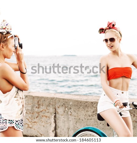 one beautiful tanned girl takes picture of her blonde sexy friend on city bike at sea shore - stock photo