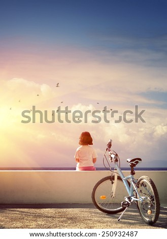 One bicycle and a little girl sitting on a wall watching the horizon - stock photo