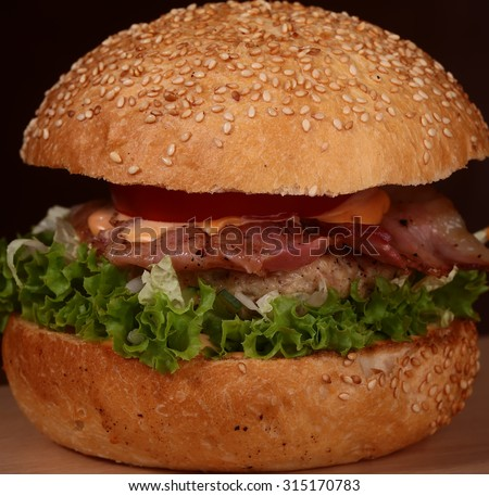 One big delicious appetizing fresh burger of green lettuce red tomato cheese and bacon slice and white bread bun with sesame seeds on bkack background closeup, square picture - stock photo