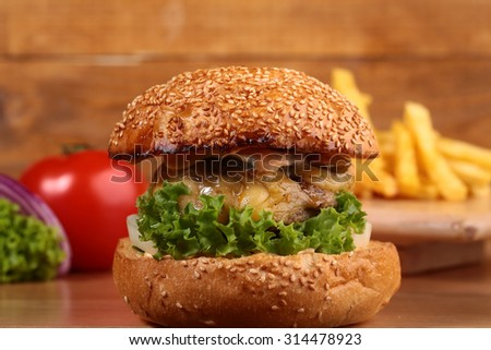 One big delicious fresh burger of green lettuce red tomato cheese meat cutlet violet onion and white bread bun with sesame seeds on wooden background closeup, horizontal picture - stock photo