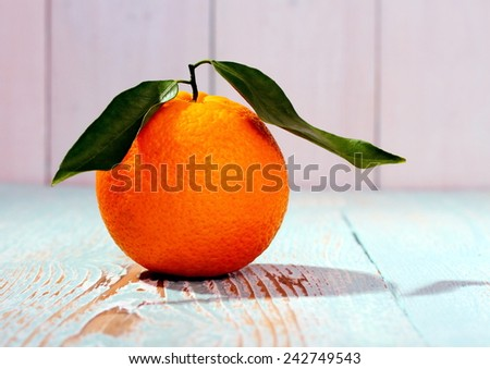 One big ripe orange fruit with leaf on wooden board, close up - stock photo