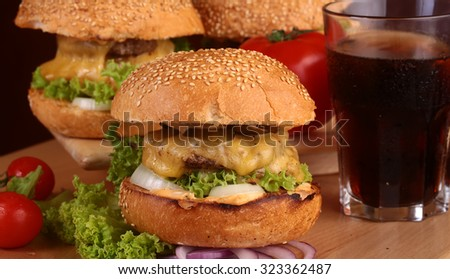 One big tasty appetizing fresh burger of green lettuce cheese bacon slice meat cutlet and white bread bun with sesame seeds and potato chips on wooden table and cola, horizontal picture - stock photo