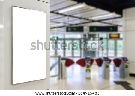 One big vertical / portrait orientation blank billboard on modern white wall with entrance of railway station background - stock photo