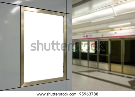 One big vertical / portrait orientation blank billboard on modern white wall with subway platform background - stock photo