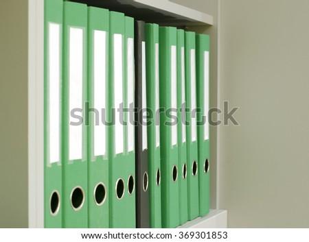 one black among the many green folder on the shelf - stock photo