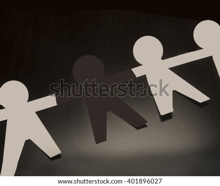 One black paper person/Targeted Human Being/Black people person  in between white cutout humanoid shapes - stock photo