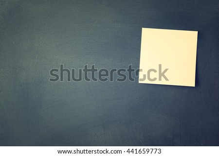 One blank sticky note attached to blackboard - stock photo