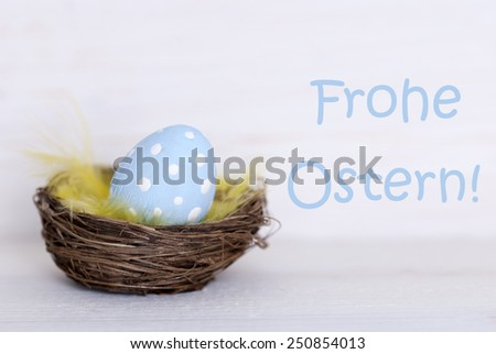 One Blue Dotted Easter Eggs In Easter Basket Or Nest On White Wooden Background With German Text Frohe Ostern Means Happy Easter As Easter Decoration Or Easter Greetings Vintage Or Old Fashion Style - stock photo
