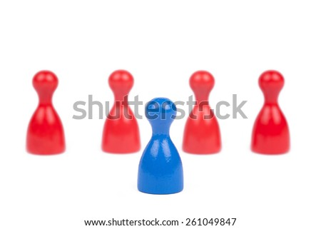 One blue Ludo figure is the frontman for four red Figures - stock photo