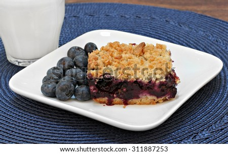 One blueberry bar cookie with streusel topping and a glass of milk.  Fresh organic blueberries on the side. - stock photo