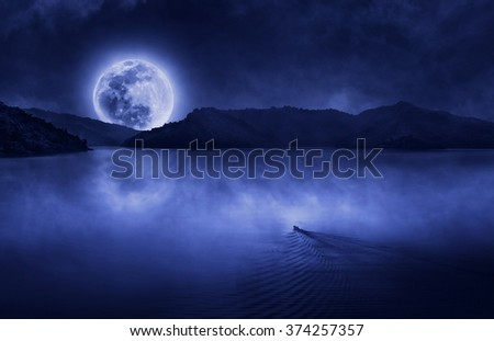 One boat run to the full moon at the dam with clouds and fog on water skin - stock photo