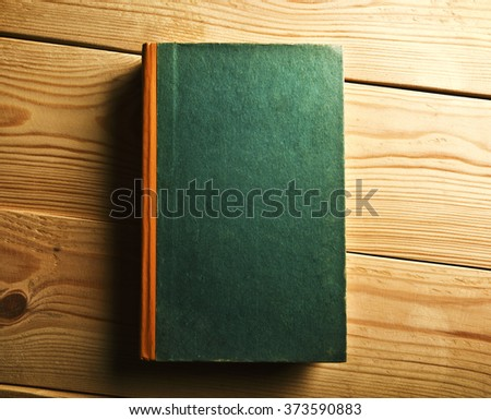 One book with empty title on wooden table - stock photo