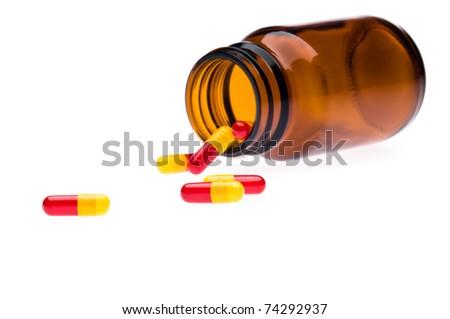 One bottle spilled pills, over white - stock photo