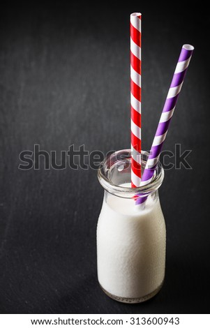 One bottle with milk on dark background with red and purple striped straws - stock photo