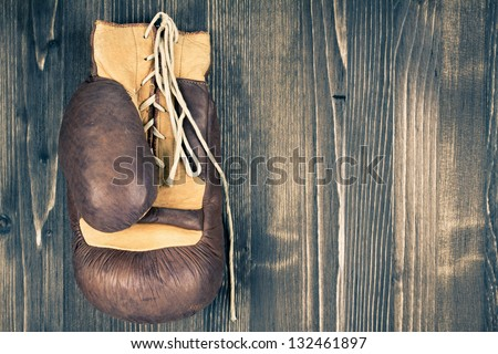 One boxing glove hanging on wood grunge background - stock photo
