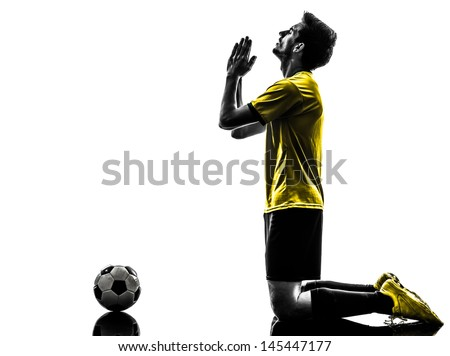 one brazilian soccer football player young man praying in silhouette studio  on white background - stock photo