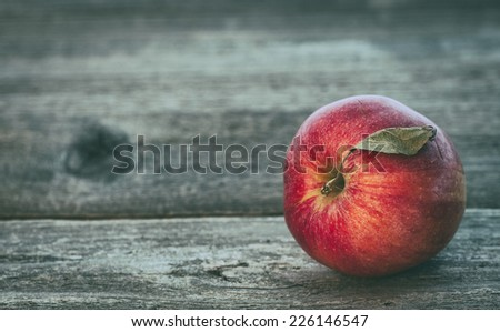One Bright Red and Ready to eat Gala Apple in Rustic Barn Setting with Old Wood Boards and room or space for copy, text, your words.  Horizontal closeup, short dept of field, vintage grunge - stock photo