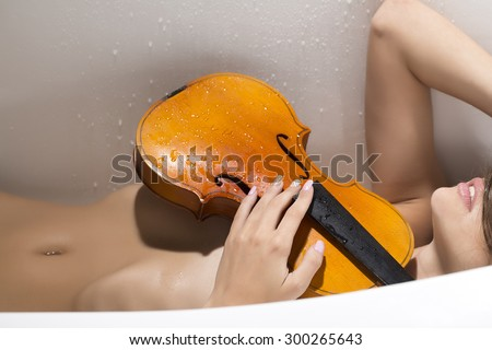 One brown wooden string musical instrument of violin in hands of young undressed girl with soft sking and tender belly lying on white bathtub background, horizontal picture - stock photo