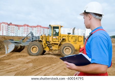 One builder worker with clipboard inspecting earthmoving works at construction site. Focus on worker - stock photo