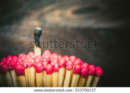 One burned match standing out from the crowd of mathes - stock photo