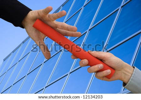 One businessman passing a red baton to another businessman over blue office building. Symbol of teamwork, helping and partnership. - stock photo