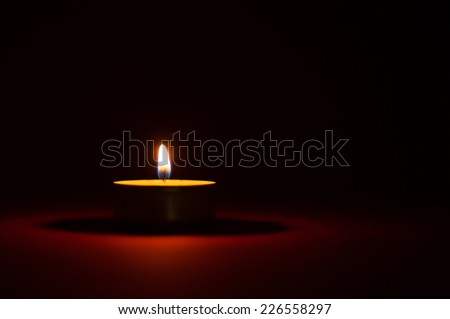 One candle burning in the dark, black and red background - stock photo