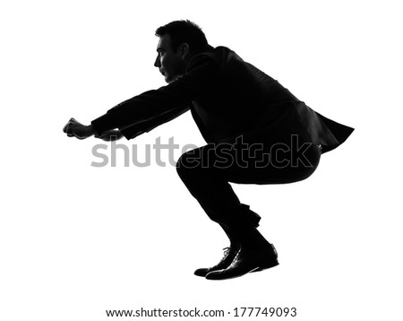 one caucasian business man driving imaginary motorcycle in silhouette on white background - stock photo