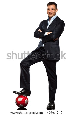 one caucasian business man standing arms crossed foot on soccer ball in studio isolated on white background - stock photo