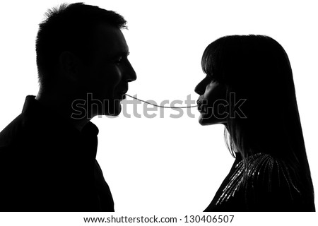 one caucasian couple man and woman eating the same spaghetti in studio silhouette isolated on white background - stock photo