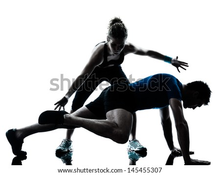 one caucasian couple man woman personal trainer coach exercising legs silhouette studio isolated on white background - stock photo