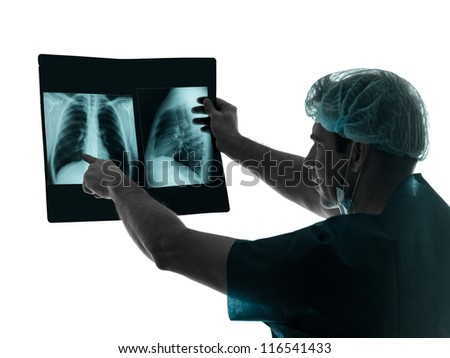 one caucasian man doctor surgeon radiologist medical examaning lung torso  x-ray image silhouette isolated on white background - stock photo
