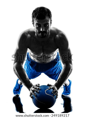 one caucasian man exercising fitness weights Medicine Ball push ups exercises in studio silhouette isolated on white background - stock photo
