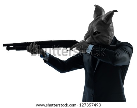 one caucasian man rabbit mask hunting with shotgun portrait in silhouette studio isolated on white background - stock photo