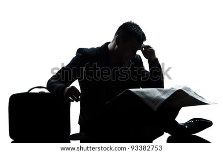 one caucasian man sitting reading newspaper despair full length silhouette in studio isolated white background - stock photo