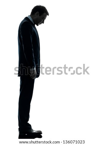 one caucasian sad business man  looking down  in silhouette studio isolated on white background - stock photo