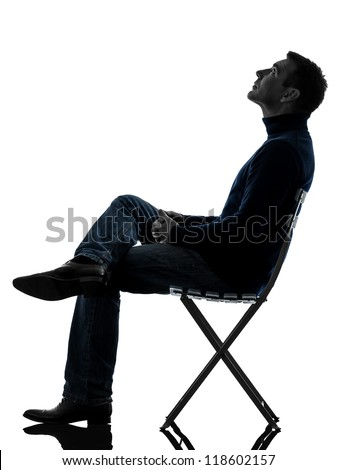 one causasian man sitting looking up   full length in silhouette studio isolated on white background - stock photo