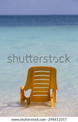 One chair standing in the water on stunning tropical beach in Morrocoy National park, Venezuela - stock photo
