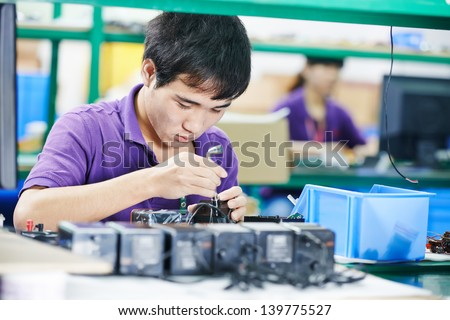 one chinese worker assembling production at line conveyor in china factory - stock photo