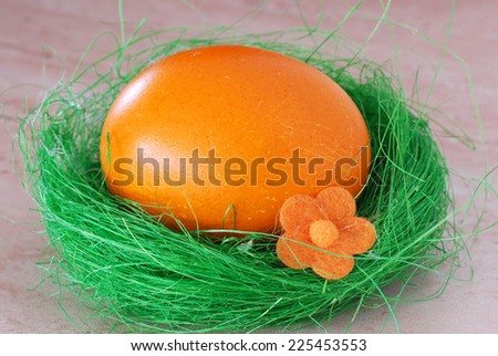 one colored orange Easter egg in green decorative nest - stock photo