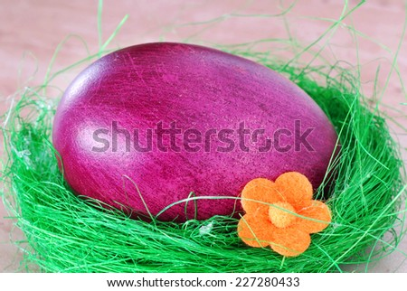 one colored purple Easter egg in decorative nest - stock photo