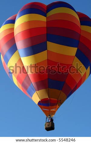 One colorful hot air balloon during early morning ascend - stock photo