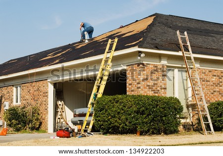 One construction worker is on the roof of a brick house repairing the damage from a tornado that came through this residential neighborhood. There are ladders and other equipment lying around. - stock photo
