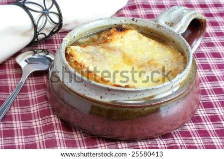 One crock of French Onion Soup with melted cheese on top. - stock photo
