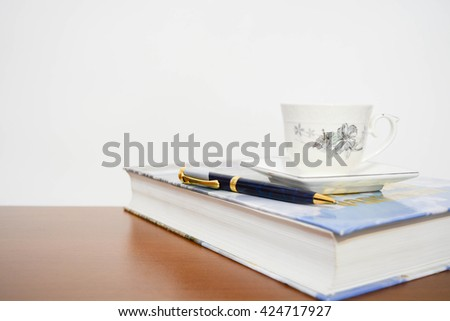 one cup of coffee book and pen on office desk - stock photo