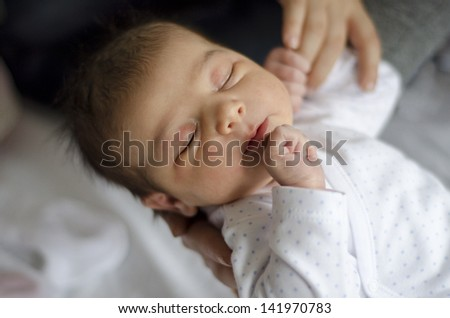 One day newborn on bed hospital, grabing hand - stock photo