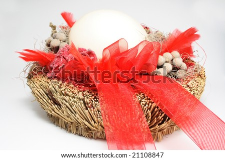 One Decorative Easter Egg in Basket with red feather - stock photo