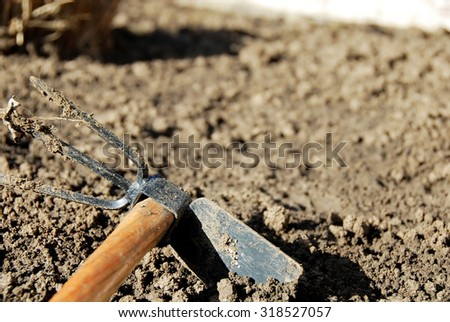 one dirty gardening hand tool - hoe in dirt closeup - stock photo
