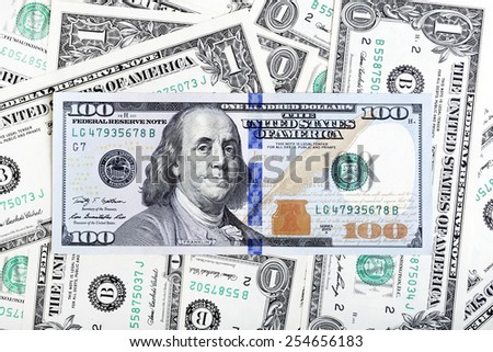One dollar bills and hundred dollar banknote macro photo. - stock photo