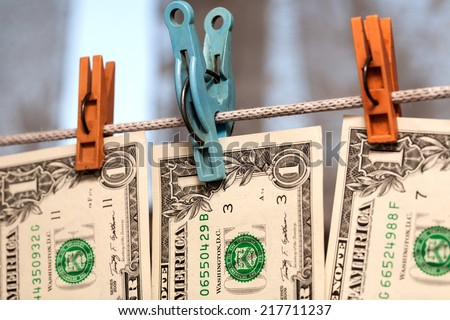 One dollar bills drying on the clothesline. The concept of money laundering - stock photo