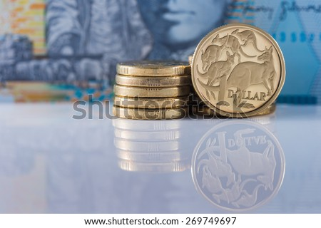 One Dollar Coin with Ten Dollar note in the background - Australian Currency - stock photo